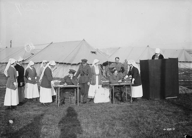 A black-and-white photograph of an outdoor polling station with 8 women lined up at 2 tables.