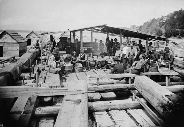 A black-and-white glass plate negative. Shown is a group of men sitting and standing on a raft that has wooden benches and a roof sheltering part of the area where the men are gathered.