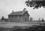 Black and white photograph of brick schoolhouse with pump in the yard, under a shade tree.