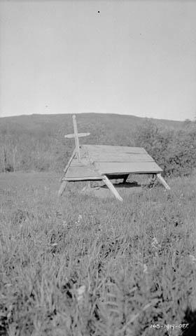 Raised burial platform in a field.