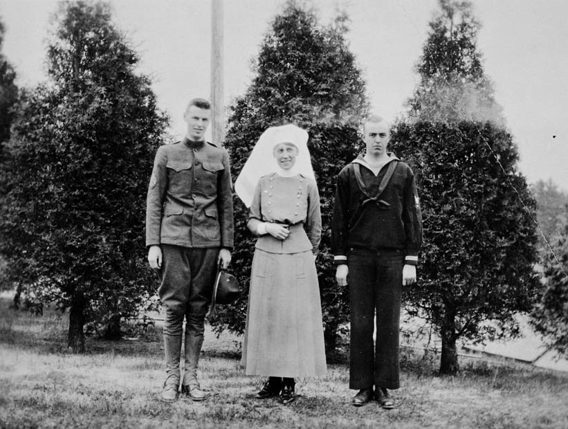 A soldier in uniform standing next to a Nursing Sister and a uniformed sailor
