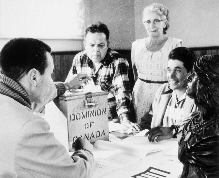 Photograph of election officers at Hiawatha Council Hall, near Rice Lake, Ontario, during the first federal election in which all adult aboriginal people in Canada could exercise their right to vote (from left to right: Lawrence Salleby, Chief Ralph Loucks, Lucy Musgrove, Eldon Muskrat), October 31, 1960