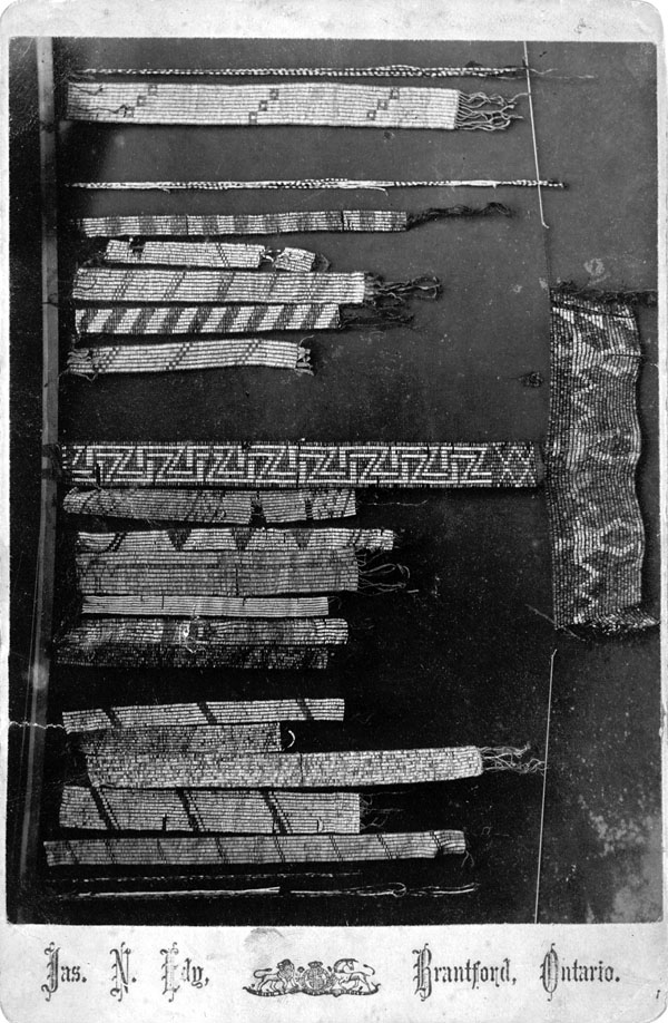 Black and white photograph of beaded belts of various sizes and designs, laying out on a surface for comparison