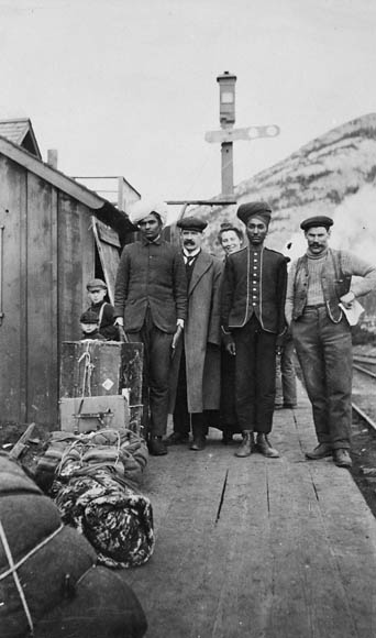 Photograph of a group including Indian immigrants at the Canadian Pacific Railway station in Frank, Alberta, circa 1903