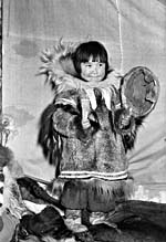 Black and white photograph of a young girl dressed in elaborate winter clothing, holding a drum