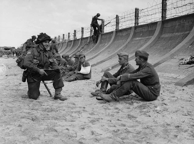 Corporal Victor Deblois of Le R�giment de la Chaudi�re guarding German prisoners on Juno Beach, Berni�res-sur-Mer, France, 6 June 1944.