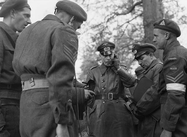 Major K. Henninger (centre), a German Army signals officer, speaking on a telephone linkup between Canadian and German forces, Wageningen, Netherlands, 5 May 1945.