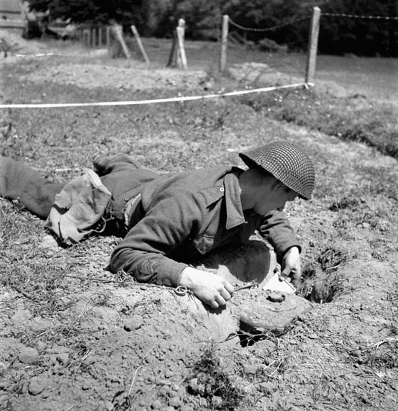 Sapper C.W. Stevens of the 18th Field Company, Royal Canadian Engineers (R.C.E.), using a mirror to locate the igniters underneath a German Teller mine, France, 22 June 1944.