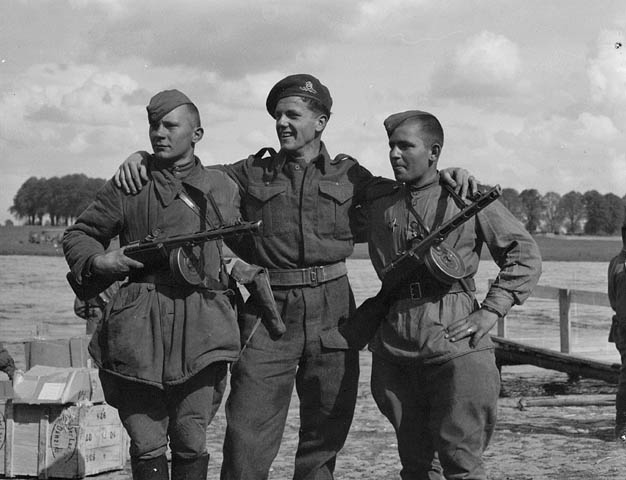 Gunner Brian O�Regan of No. 3 Public Relations Group with two Russian soldiers during the linkup of Russian and American armies at Torgau, Germany, 27 April 1945.
