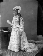 Studio photograph of Miss Richards wearing a dress decorated with the banners of Canadian newspapers, Ottawa, March 1876