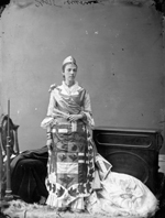 Studio photograph of Mrs. St. Denis Le Moine wearing a floor length dress, an apron decorated with maple leaves and Scottish thistles, and a small beaver sculpture on her right shoulder, Ottawa, March 1876