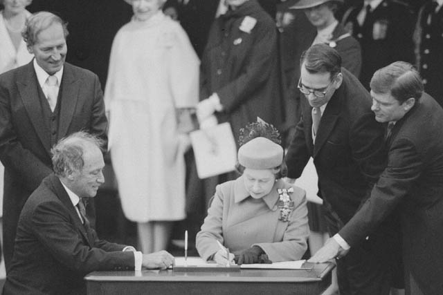 Photograph of Her Majesty Queen Elizabeth II with Prime Minister Pierre Elliott Trudeau signing the Proclamation of the CONSTITUTION ACT, 1982, April 17, 1982