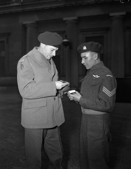 Lieutenant-Colonel J.F.R. Akehurst, Commanding Officer,  2nd Battalion, First Special Service Force, examines Sergeant Tommy Prince�s Military Medal, which was awarded  for �distinguished and gallant service� at Anzio. Buckingham Palace, London, England, 12 February 1945.