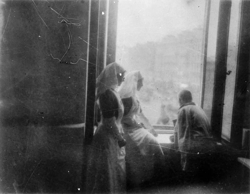 Two nursing sisters and a man in a jacket looking out of a window