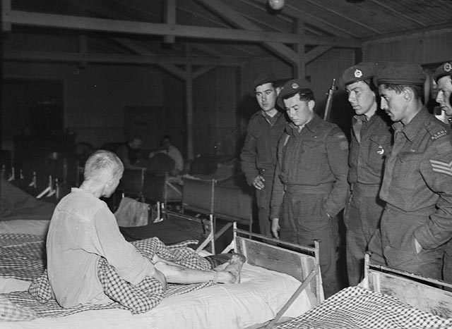Photograph of Canadian soldiers with a malnourished prisoner in a concentration camp near Weener, Germany, liberated by the 3rd Canadian Infantry Division, April 24, 1945