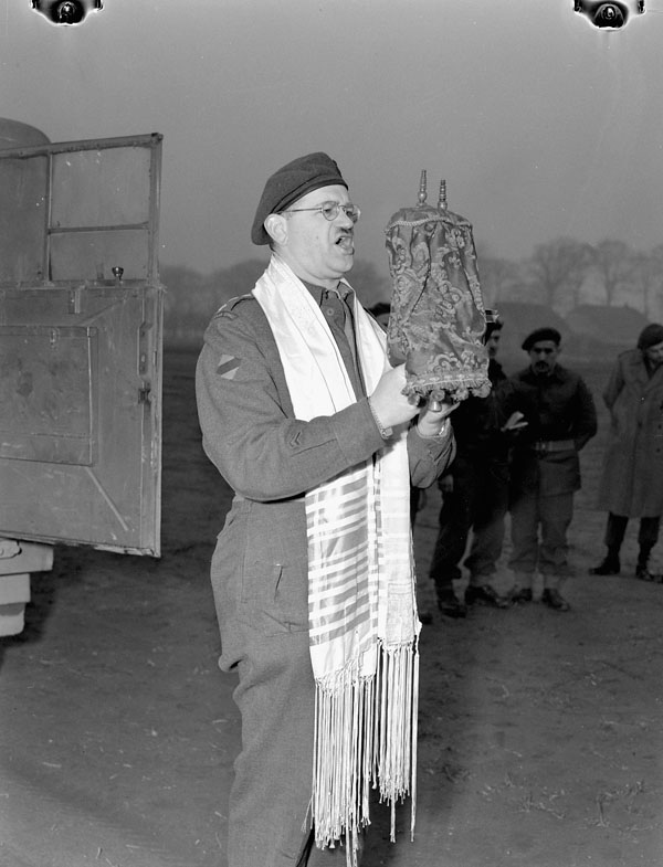 Photograph of Honourary Captain Samuel Cass, a rabbi, conducting the first worship service celebrated on German territory by Jewish personnel of the 1st Canadian Army, March 18, 1945