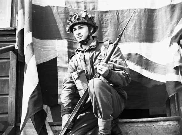 Photograph of man wearing army uniform and camouflage helmet, holding a rifle and kneeling in front of Union Jack flag