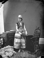 Studio photograph of Miss Janet Scott wearing a hat fringed with coins, an embroidered vest and skirt with appliqué, Ottawa, March 1876