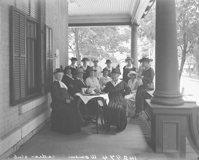 Group of women posing for a photo on a veranda.