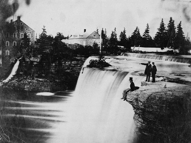A black-and-white photograph of the view looking across the Rideau Falls. A man in a top hat is sitting on the near bank with two other gentlemen standing behind. On the far bank are buildings belonging to the McKay and McKinnon cloth mill.