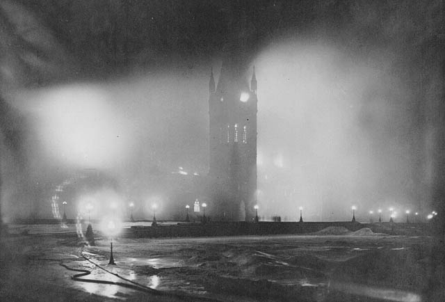 A black-and-white photograph of the Centre Block of the Parliament Buildings taken at 12:30 a.m. The view is hazy with the Centre Block lit through the smoke by many lights.