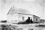 Black and white photograph of a wooden prairie house with a sloped roof and three people sitting outside on a porch