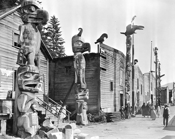 Black and white photograph of a street scene with large wooden houses and totem poles lining the wooden walkway in front of each house