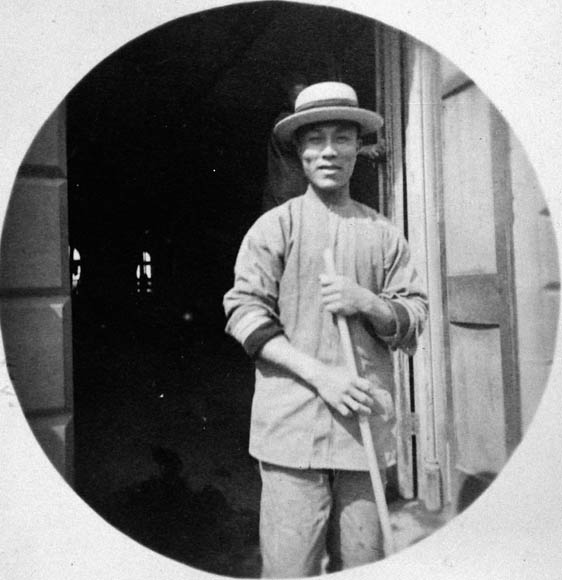 Photograph of smiling man wearing a straw boater hat and holding broom, standing in open doorway