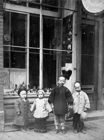 Photograph of four children in traditional Chinese clothing, standing in front of store