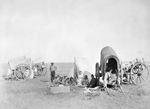 Black and white photograph of a prairie landscape, with several covered carts, tents, and a seated group of people