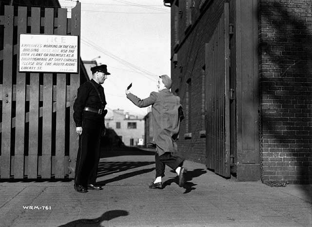 Photograph of a munitions worker showing her pass to the security guard at the gate of the John Inglis Co. Bren gun plant. A sign at left instructs employees to use the route along Liberty Street. May 10, 1941