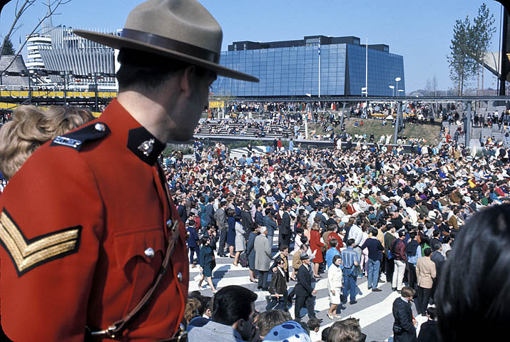 Photograph of a Royal Canadian Mounted Police officer and crowd in front of the Quebec Pavilion at Expo 67, 1967