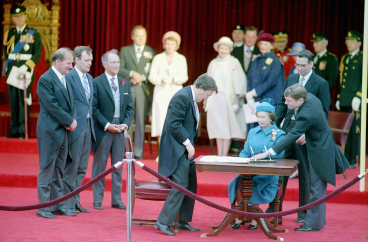Photograph of officials signing the Proclamation of the CONSTITUTION ACT, 1982, on Parliament Hill, Ottawa (from left to right: Gerald Regan, Minister of Labour; Jean Chrétien, Minister of Justice; Pierre Elliott Trudeau, Prime Minister of Canada; André Ouellet, Registrar General; Queen Elizabeth the Second; Michael Pitfield, Clerk of the Privy Council), April 17, 1982