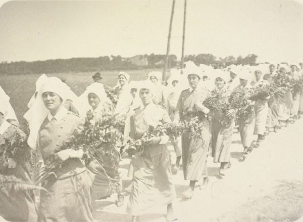 Anne E.Ross is the nursing sister closest to the left of the procession of nursings sisters, all are carrying bouquets of flowers