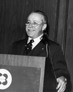 Photograph of Dr. Gustave Gingras speaking from behind a podium