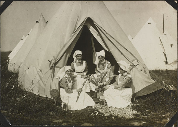 Four nursing sisters sitting in front of a tent arranging flowers.