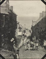 Photograph of pedestrians and a donkey on a steep and narrow street in Clovelly, England, unknown date