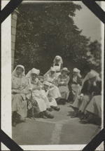 Photograph of nine nursing sisters sitting outdoors, Joinville-le-Pont, France, June 1918
