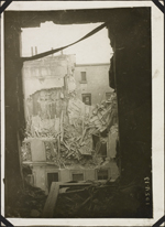 Photograph of a bombed building, taken through the window of another damaged building, Paris, France, March 1918