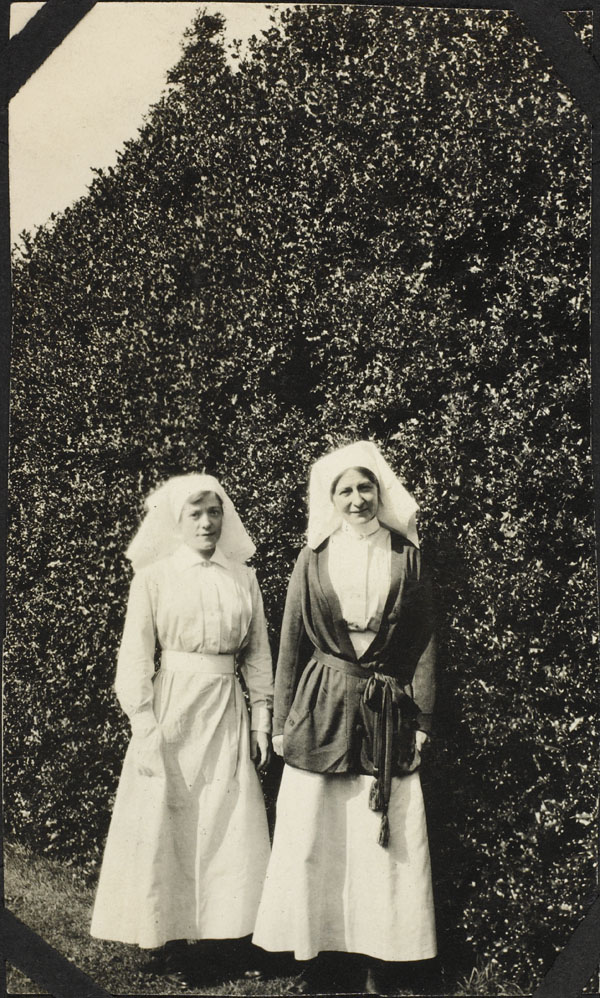 Two nursing sisters standing in front of a hedge