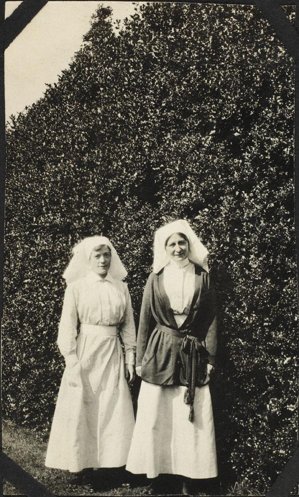 Deux femmes debout devant des arbustes