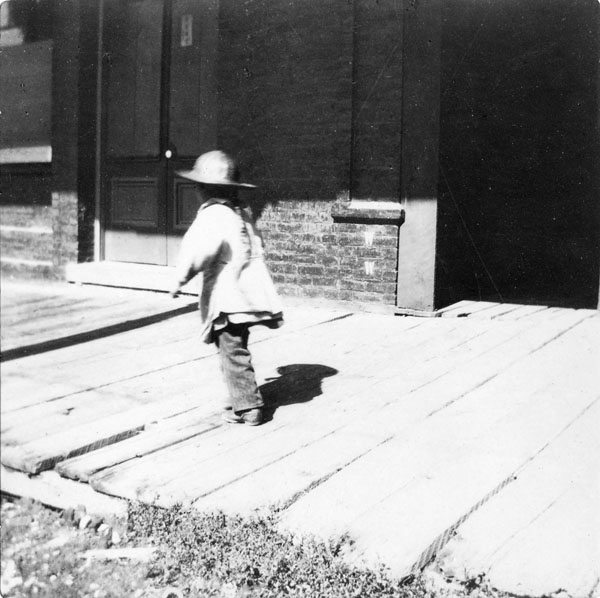 Photograph of small child wearing hat and walking away on wooden sidewalk in front of stores