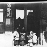 Photographie de quatre enfants portant le costume traditionnel chinois, debout devant une porte de magasin en brique