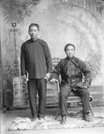 Studio photograph of two young men in traditional  Chinese clothing. One standing and holding book, one seated